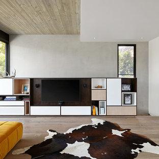 Imagen de salón abierto, nórdico, con paredes blancas, pared multimedia y suelo de madera clara