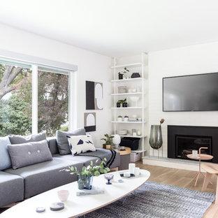 Esempio di un soggiorno scandinavo chiuso con sala formale, pareti bianche, parquet chiaro, camino classico, cornice del camino in mattoni, TV a parete e pavimento beige