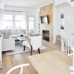 他の地域の小さい北欧スタイルのおしゃれなLDK (白い壁、淡色無垢フローリング、標準型暖炉、木材の暖炉まわり、壁掛け型テレビ、白い床) の写真