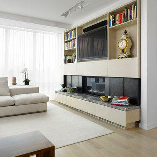 This is an example of a large scandinavian open plan living room in Toronto with white walls, light hardwood flooring, a standard fireplace and a built-in media unit.