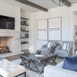 Inspiration för maritima vardagsrum, med vita väggar, mellanmörkt trägolv, en standard öppen spis, en väggmonterad TV och brunt golv