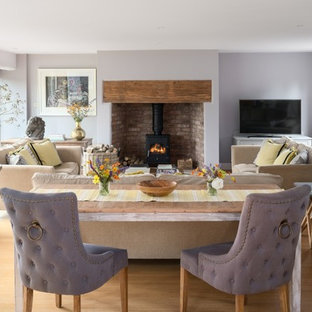 Inspiration for a mid-sized transitional enclosed light wood floor and beige floor living room remodel in Cheshire with purple walls, a wood stove, a brick fireplace and a tv stand