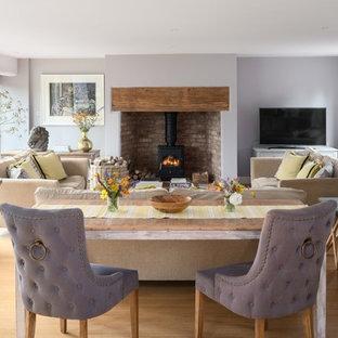 Modelo de salón cerrado, clásico renovado, de tamaño medio, con paredes púrpuras, suelo de madera clara, estufa de leña, marco de chimenea de ladrillo, televisor independiente y suelo beige