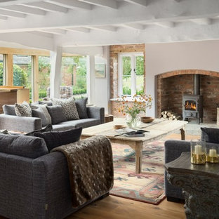 This is an example of a medium sized rural enclosed living room in Cheshire with beige walls, light hardwood flooring, a wood burning stove and beige floors.