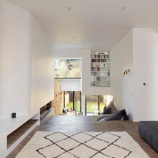 ロンドンの広いコンテンポラリースタイルのおしゃれなLDK (ライブラリー、白い壁、無垢フローリング、横長型暖炉、コンクリートの暖炉まわり、壁掛け型テレビ) の写真