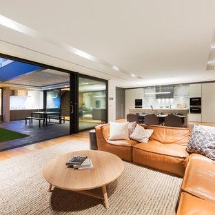 Foto på ett stort funkis allrum med öppen planlösning, med en väggmonterad TV