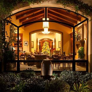 サンディエゴの中サイズの地中海スタイルのおしゃれなLDK (フォーマル、ベージュの壁、大理石の床、標準型暖炉、漆喰の暖炉まわり、テレビなし、ベージュの床) の写真