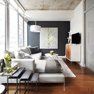Inspiration for a small eclectic loft-style medium tone wood floor living room remodel in New York with white walls and a wall-mounted tv