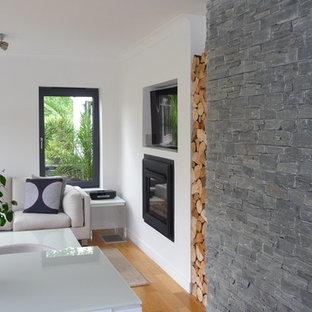 Esempio di un soggiorno nordico di medie dimensioni e aperto con pareti grigie, parquet scuro, stufa a legna, cornice del camino in intonaco e TV nascosta