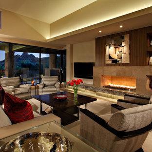 Esempio di un grande soggiorno moderno aperto con pareti beige, pavimento in pietra calcarea, camino classico, cornice del camino in pietra, TV a parete e sala formale