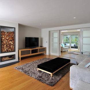 Modelo de salón para visitas abierto, marinero, con paredes blancas, suelo de madera clara, estufa de leña y televisor independiente