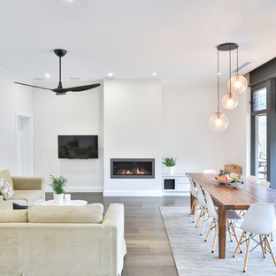This is an example of a large contemporary open concept living room in Sydney with white walls, medium hardwood floors, a metal fireplace surround, a wall-mounted tv, brown floor and a ribbon fireplace.