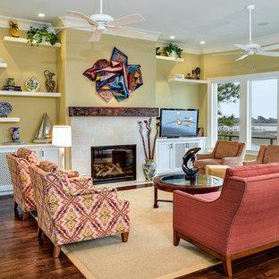 チャールストンのトロピカルスタイルのおしゃれなLDK (黄色い壁、濃色無垢フローリング、標準型暖炉、タイルの暖炉まわり、据え置き型テレビ) の写真