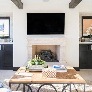 オレンジカウンティの中サイズのビーチスタイルのおしゃれなLDK (ベージュの壁、トラバーチンの床、標準型暖炉、石材の暖炉まわり、壁掛け型テレビ) の写真