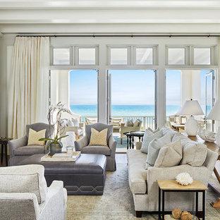 タンパのビーチスタイルのおしゃれなリビング (白い壁、淡色無垢フローリング、標準型暖炉、茶色い床) の写真