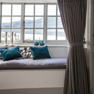 Inspiration for a medium sized coastal enclosed living room in Kent with white walls, medium hardwood flooring and a stone fireplace surround.