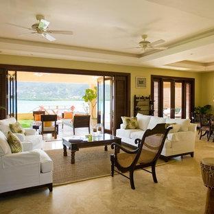 Foto di un grande soggiorno tropicale aperto con pareti beige e pavimento in travertino