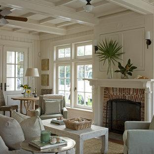 他の地域のビーチスタイルのおしゃれなリビング (白い壁、無垢フローリング、標準型暖炉、レンガの暖炉まわり、内蔵型テレビ、白い床) の写真