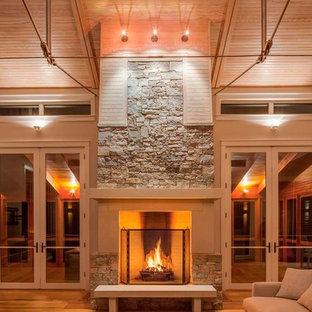 Modelo de salón abierto, moderno, grande, con paredes beige, suelo de madera clara, chimenea tradicional y marco de chimenea de piedra