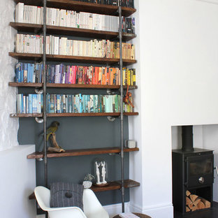 Trendy dark wood floor living room library photo in Manchester with white walls
