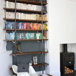 Idée de décoration pour un salon avec une bibliothèque ou un coin lecture design avec un mur blanc et un sol en bois foncé.