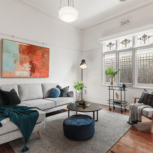 This is an example of a classic living room in Melbourne with white walls, medium hardwood flooring and brown floors.