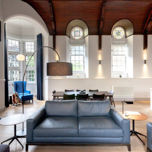 This is an example of a contemporary open plan living room in Edinburgh with white walls, light hardwood flooring, a standard fireplace, beige floors, a vaulted ceiling and wainscoting.