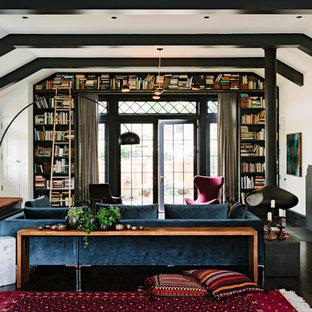 Bild på ett amerikanskt vardagsrum, med ett bibliotek, en hängande öppen spis, vita väggar, mörkt trägolv och svart golv