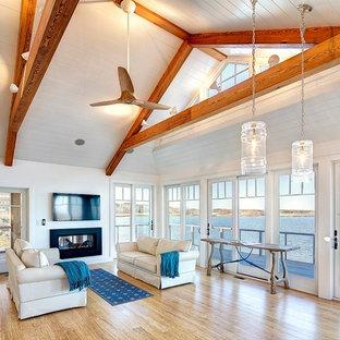 ボストンの大きいビーチスタイルのおしゃれなLDK (白い壁、竹フローリング、標準型暖炉、金属の暖炉まわり、壁掛け型テレビ) の写真