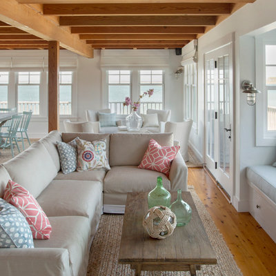 Example of a beach style open concept medium tone wood floor living room design in Boston with white walls