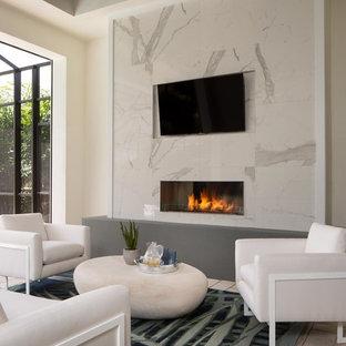 マイアミのコンテンポラリースタイルのおしゃれなリビング (ベージュの壁、横長型暖炉、壁掛け型テレビ、ベージュの床) の写真