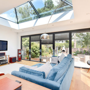 Inspiration for a contemporary living room in Hampshire with white walls, medium hardwood flooring and brown floors.