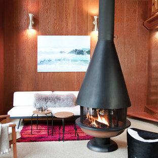 Imagen de salón tipo loft, rural, de tamaño medio, sin televisor, con paredes marrones, moqueta, chimeneas suspendidas y suelo blanco