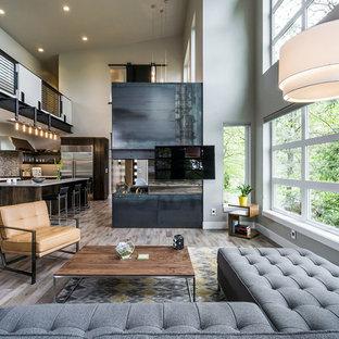 Foto di un grande soggiorno moderno aperto con pareti grigie, pavimento in legno massello medio, camino bifacciale e TV a parete