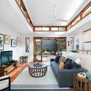 Foto di un soggiorno classico di medie dimensioni e aperto con pareti bianche, pavimento in terracotta, nessun camino, TV autoportante e pavimento rosso