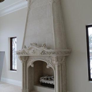 デトロイトのヴィクトリアン調のおしゃれなリビング (ベージュの壁、トラバーチンの床、標準型暖炉、コンクリートの暖炉まわり、ベージュの床) の写真