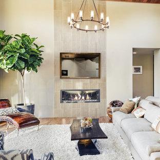 Modelo de salón para visitas abierto, bohemio, de tamaño medio, con paredes beige, suelo de madera clara, chimenea de doble cara, marco de chimenea de metal, televisor retractable y suelo marrón