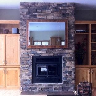 Esempio di un soggiorno di medie dimensioni e chiuso con libreria, pareti marroni, camino classico, cornice del camino in pietra, TV nascosta e pavimento marrone