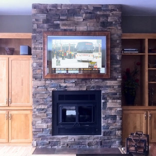 Mid-sized elegant enclosed light wood floor and brown floor living room library photo in Other with gray walls, a standard fireplace, a stone fireplace and a concealed tv