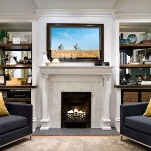 Foto de biblioteca en casa cerrada, grande, con paredes blancas, suelo de madera clara, chimenea tradicional, marco de chimenea de madera, televisor retractable y suelo beige