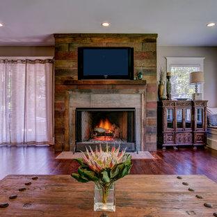 Immagine di un soggiorno boho chic di medie dimensioni e aperto con pareti beige, parquet scuro, camino classico, cornice del camino in legno e TV a parete