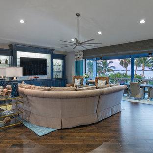 マイアミの中くらいのビーチスタイルのおしゃれなLDK (グレーの壁、濃色無垢フローリング、暖炉なし、壁掛け型テレビ) の写真