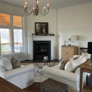 オマハの広いトランジショナルスタイルのおしゃれなLDK (黄色い壁、濃色無垢フローリング、コーナー設置型暖炉、タイルの暖炉まわり、茶色い床) の写真