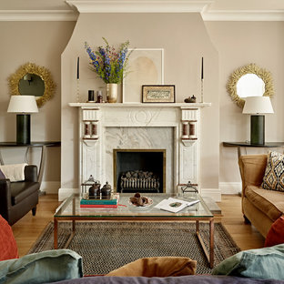 This is an example of a medium sized traditional open plan living room in London with beige walls, a standard fireplace, a stone fireplace surround, medium hardwood flooring and brown floors.