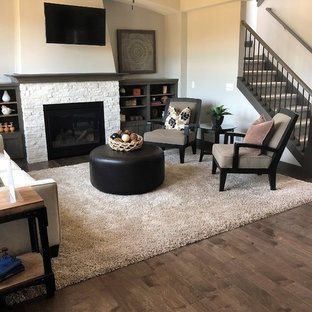 Living room - mid-sized craftsman open concept medium tone wood floor and brown floor living room idea in Minneapolis with beige walls, a standard fireplace, a stone fireplace and a wall-mounted tv