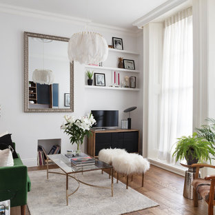 This is an example of a scandi living room with white walls, medium hardwood flooring, a freestanding tv and brown floors.