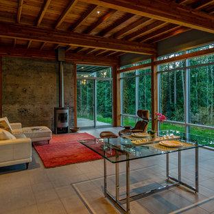 Foto de salón para visitas abierto, moderno, de tamaño medio, sin televisor, con paredes grises, estufa de leña, suelo de baldosas de porcelana, marco de chimenea de metal y suelo gris