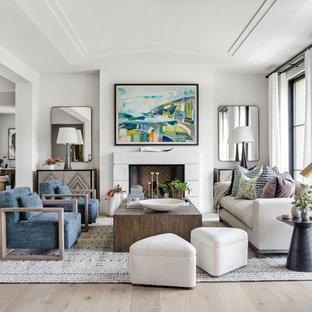 オレンジカウンティの中サイズのトランジショナルスタイルのおしゃれなLDK (白い壁、淡色無垢フローリング、標準型暖炉、漆喰の暖炉まわり、フォーマル、テレビなし) の写真