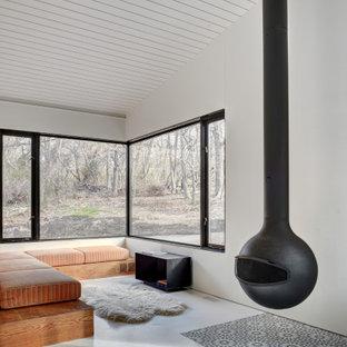 ニューヨークのモダンスタイルのおしゃれなLDK (白い壁、吊り下げ式暖炉、白い床、三角天井、塗装板張りの壁) の写真
