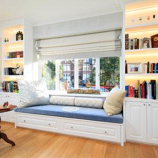 На фото: изолированная гостиная комната среднего размера в классическом стиле с библиотекой, фиолетовыми стенами и полом из ламината без ТВ